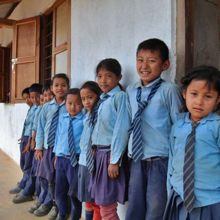 A group of young students in Nepal stand in a line against a school