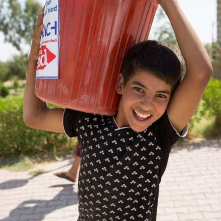 Boy carries a container of emergency supplies with the Christian Aid logo on, in Iraq.