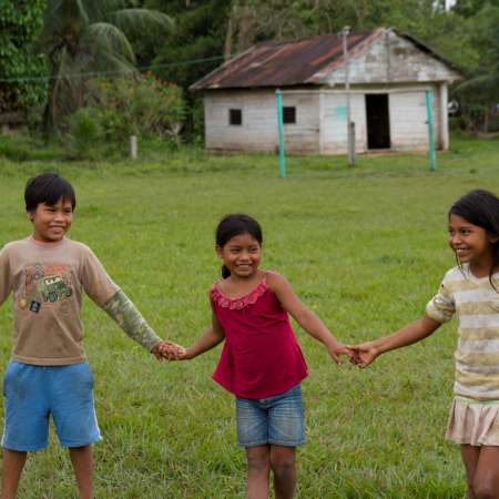 Three children from Capaina community holding hands and playing out by the schoolhouse