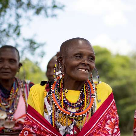 Local woman sits in traditional dress in her Maasai village, Narok County Kenya