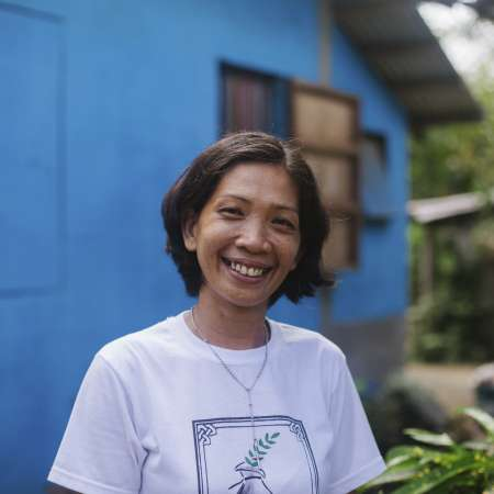 Sussett stands by the row of new typhoon resilient homes built with the support of Christian Aid partner ICODE