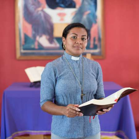 Deacon Elineide Ferreira de Oliveira holding bible and smiling.