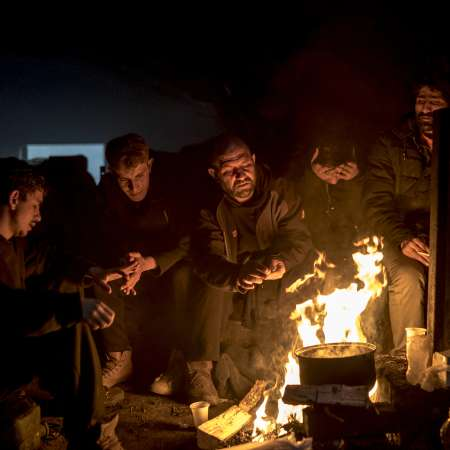 Five men sitting around a campfire in the dark.