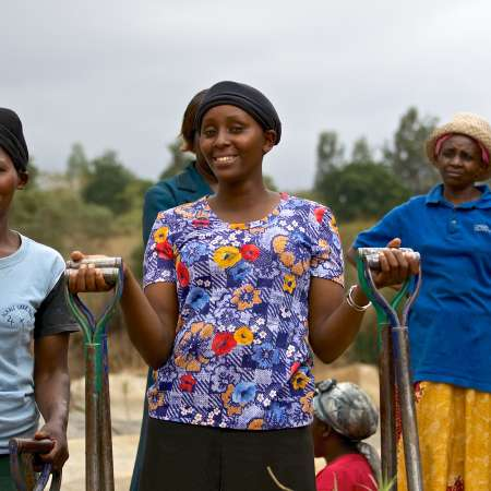 Climate change in Kenya, women in field ready to harvest their crops