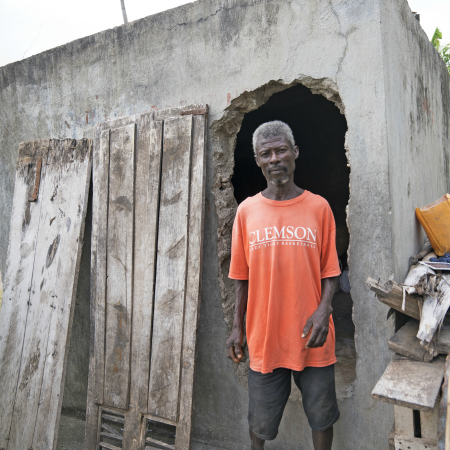 Marcelin stands outside his house in Haiti