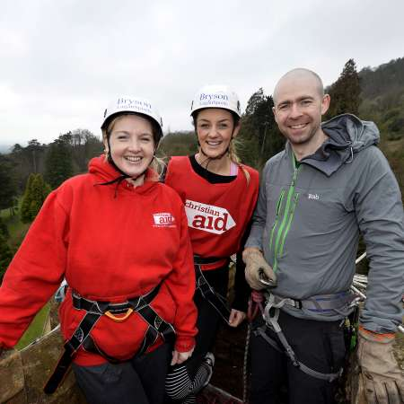MMA World champion Leah McCourt and Christian Aid's Chief Executive abseiled Belfast Castle