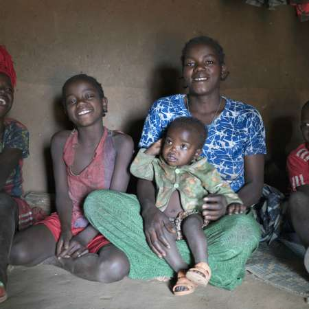 Aster and her children inside their home in Ethiopia