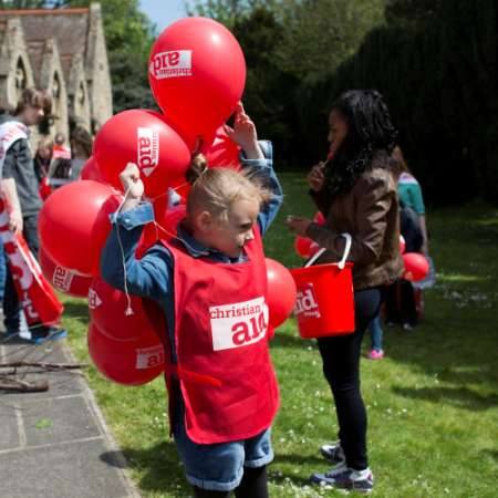 Young girl with Christian Aid Week Balloons